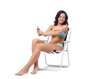 Lycklig kvinna som solbadar och applicerar sunscreen Arkivbild