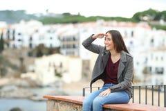 Lycklig kvinna som spanar på en avsats på semester arkivbild