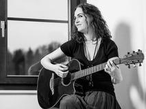 Lycklig kvinna som spelar den akustiska gitarren Arkivbilder