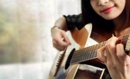 Lycklig kvinna som spelar en akustisk gitarr i huset, avkoppling och fotografering för bildbyråer