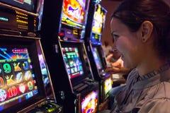Lycklig kvinna som spelar enarmade banditer i kasino Royaltyfri Foto
