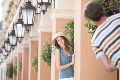 Lycklig kvinna som spelar kurragömma med mannen bland pelare Fotografering för Bildbyråer