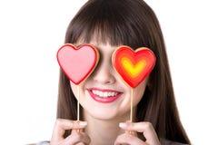 Lycklig kvinna som spelar med hjärta formade kex arkivbilder