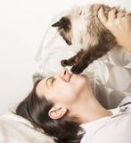 Lycklig kvinna som spelar med katten Fotografering för Bildbyråer