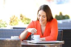 Lycklig kvinna som stitting en drink i en coffee shop fotografering för bildbyråer
