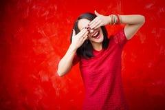 Lycklig kvinna som täcker henne ögon med båda händer royaltyfri bild