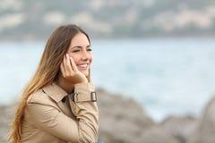 Lycklig kvinna som tänker och ser bort på havet Royaltyfri Foto