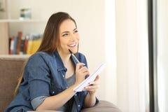 Lycklig kvinna som tänker vad för att skriva i en anteckningsbok royaltyfri foto