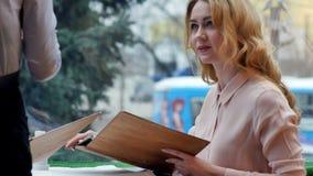Lycklig kvinna som talar med uppassaren som sitter i tabellen av ett kafé Royaltyfri Bild