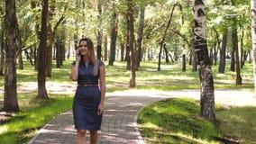 Lycklig kvinna som talar på mobiltelefonen, utomhus Flicka som talar på telefonen som går i parkera attraktivt kvinnabarn stock video