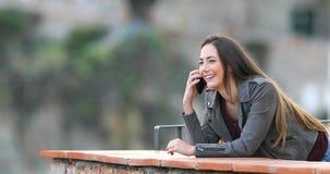 Lycklig kvinna som talar på telefonen i en balkong