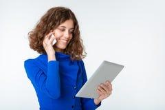Lycklig kvinna som talar på telefonen och använder minnestavladatoren Royaltyfria Foton