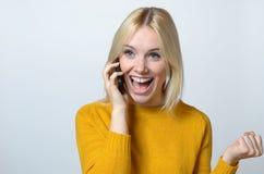 Lycklig kvinna som talar till någon över telefonen Arkivfoto
