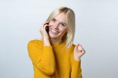 Lycklig kvinna som talar till någon över telefonen Fotografering för Bildbyråer