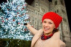 Lycklig kvinna som tar foto av julgranen i Florence, Italien Royaltyfri Fotografi