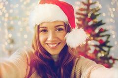 Lycklig kvinna som tar selfie över julträd Arkivfoton