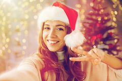 Lycklig kvinna som tar selfie över julträd Fotografering för Bildbyråer