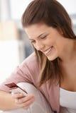 Lycklig kvinna som texting på den mobila telefonen Arkivfoto