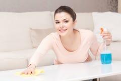 Lycklig kvinna som torkar den vita tabellen royaltyfri fotografi