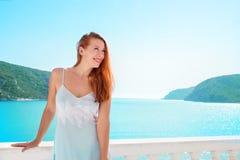 Lycklig kvinna som tycker om den lyxiga semesterorten på havet arkivbild