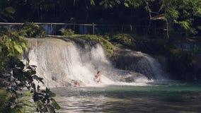 Lycklig kvinna som tycker om flödande vatten från den tropiska vattenfallet Ung kvinna som badar i vattenfallet, flödande strömva stock video