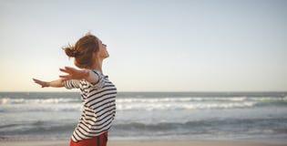 Lycklig kvinna som tycker om frihet med öppna händer på havet Arkivfoton