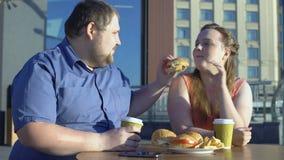 Lycklig kvinna som tycker om hamburgaresmak, fett par som utomhus äter snabbmat i kafé stock video