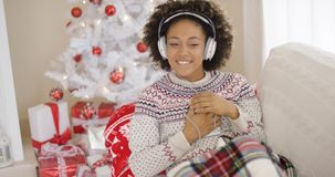 Lycklig kvinna som tycker om hennes musik på jul Royaltyfri Foto