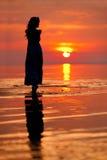Lycklig kvinna som tycker om i havssolnedgång Silhouetted mot solarna Royaltyfri Fotografi