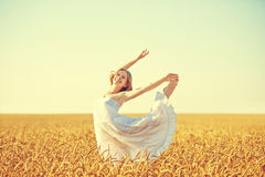 Lycklig kvinna som tycker om liv i guld- vetefält Royaltyfri Foto