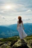 Lycklig kvinna som tycker om naturen i bergen Royaltyfria Bilder
