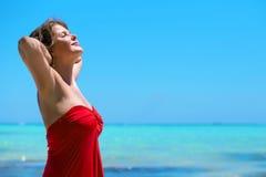 Lycklig kvinna som tycker om sommar vid havet arkivbild