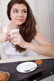 Lycklig kvinna som tycker om tea och kakor Royaltyfri Foto