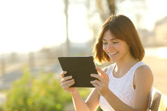 Lycklig kvinna som utomhus använder en minnestavla Royaltyfria Bilder