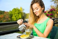Lycklig kvinna som utomhus gör grönt te Arkivbild