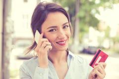 Lycklig kvinna som utomhus köper online-danande en oder med en smart telefon arkivfoto
