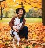 Lycklig kvinna som utomhus spelar med hunden i höst Royaltyfria Bilder