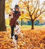 Lycklig kvinna som utomhus spelar med hundkapplöpning i höst Arkivbild