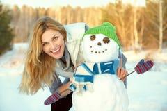 Lycklig kvinna som utomhus spelar med snögubben i vintern arkivbilder