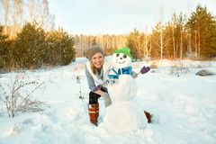 Lycklig kvinna som utomhus spelar med snögubben i vintern fotografering för bildbyråer