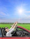 Lycklig kvinna som vilar på hjulet av en bil på en landsväg på s Royaltyfri Foto