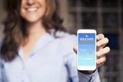 Lycklig kvinna som visar en mobiltelefon med förutsett väder i Royaltyfri Foto