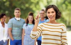 Lycklig kvinna som visar ett finger eller pekar upp arkivbilder