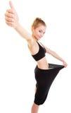 Lycklig kvinna som visar hur mycket vikt henne som är borttappad, stora flåsanden Arkivbild