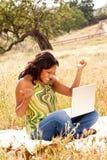 Lycklig kvinna utanför på en dator Royaltyfri Foto