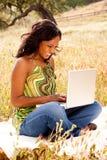 Lycklig kvinna utanför på en dator Royaltyfri Fotografi