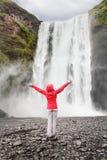 Lycklig kvinna vid vattenfallet Skogafoss på Island Arkivbilder
