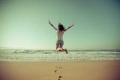 Lycklig kvinnabanhoppning på stranden Arkivfoto