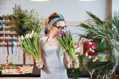 Lycklig kvinnablomsterhandlare som luktar tulpan i blomsterhandel Arkivbild