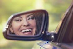 Lycklig kvinnachaufför som ser, i att skratta för spegel för bilsidosikt royaltyfri fotografi